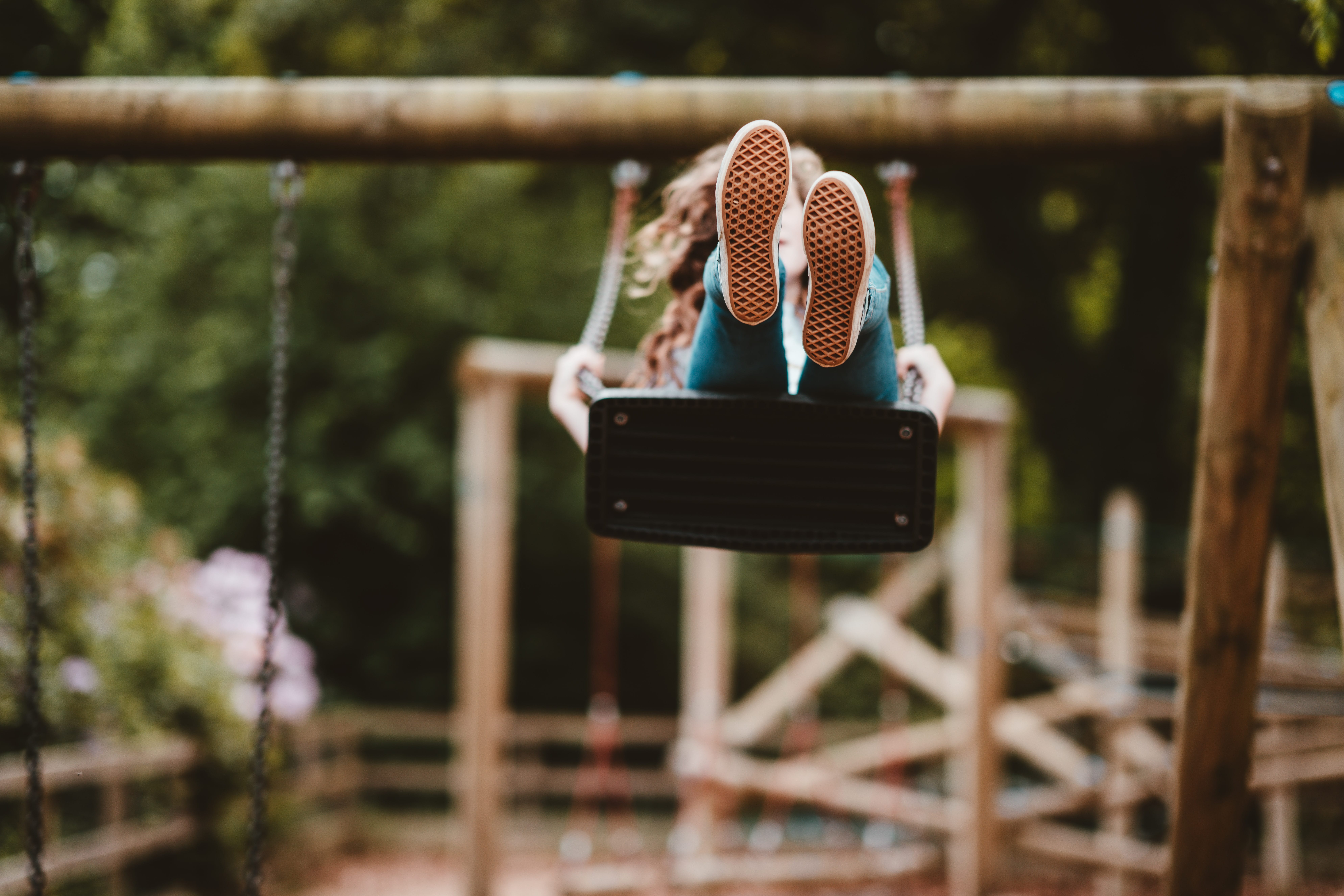 Child in mid-air swinging on a swing with feet pointing at the camera