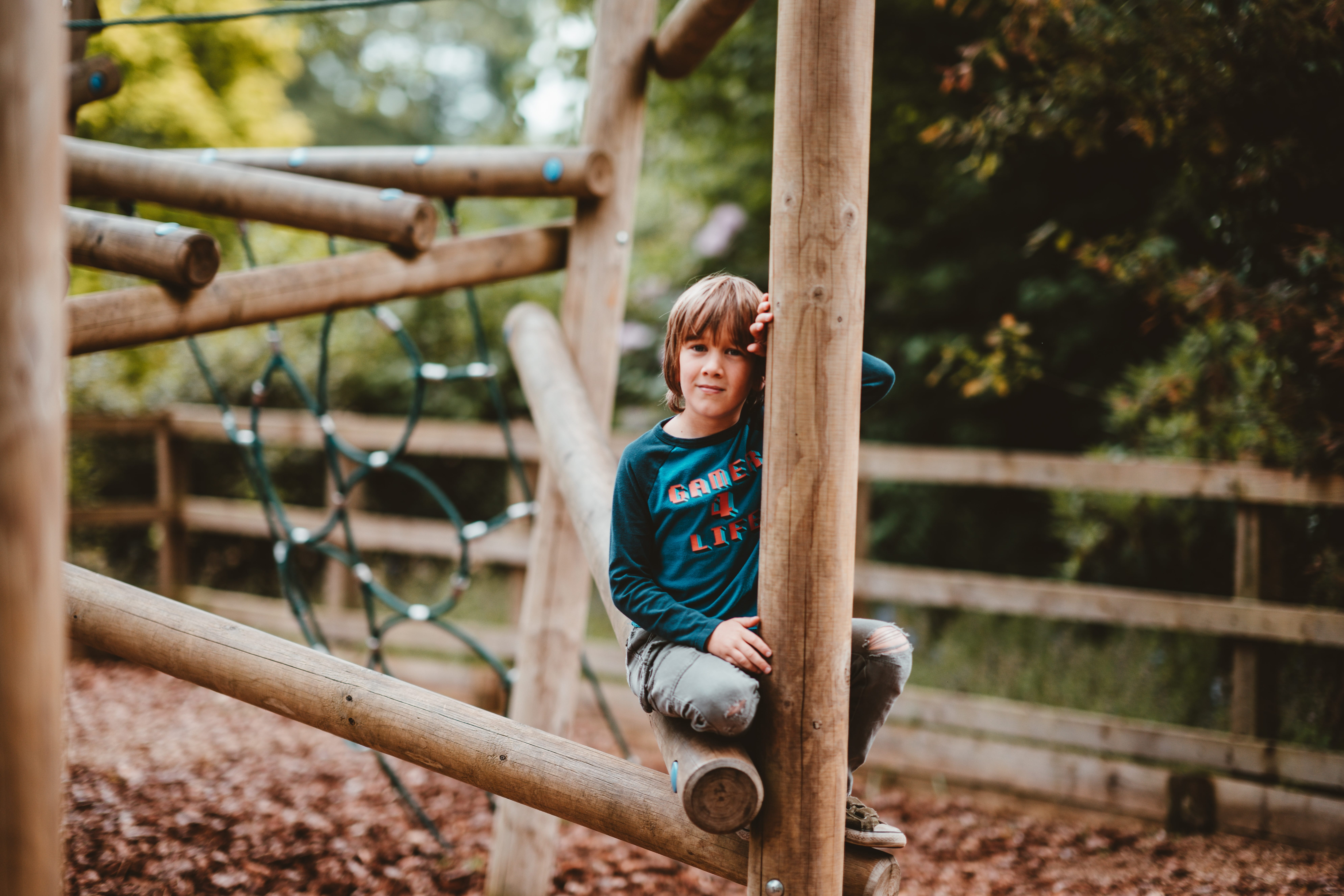 A child sat on a wooden climbing frame looking at the camera