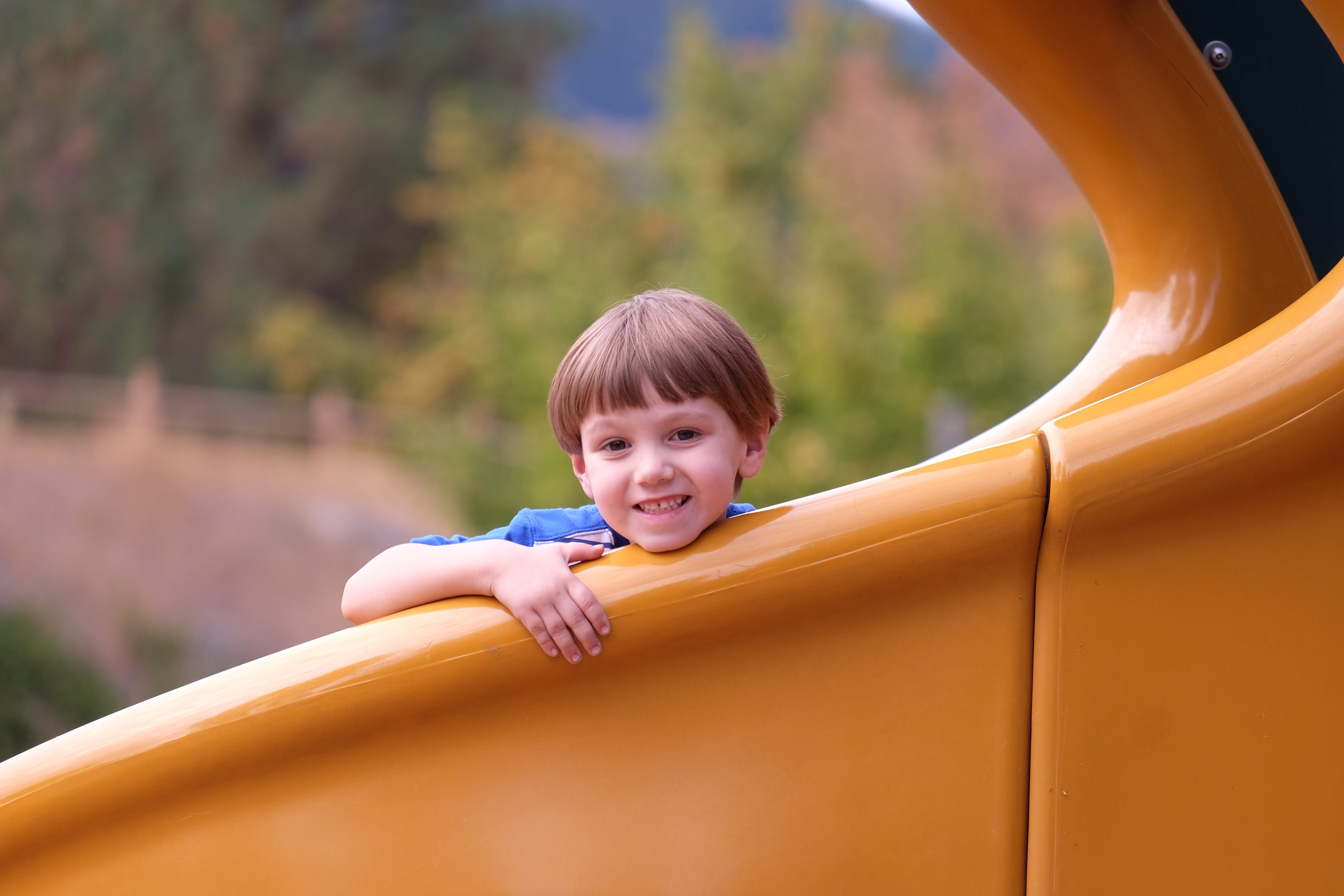 CHild looking over the edge of a slide at the camera